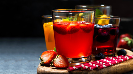 fruit and berry beverages in assortment on dark background