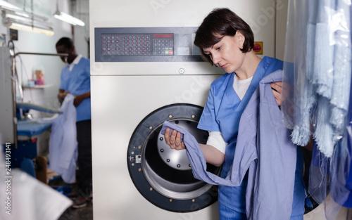 Female worker inspecting garments