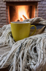 Cozy scene before fireplace with mug of hot drink and wool warm scarf.