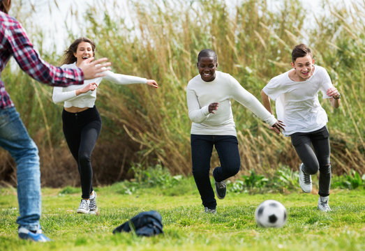 Portrait of  four friends posing on countryside field with ball