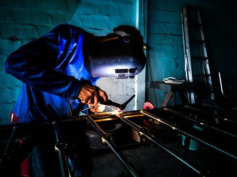 Picture of mechanic welding aluminum door with electric welding machine.