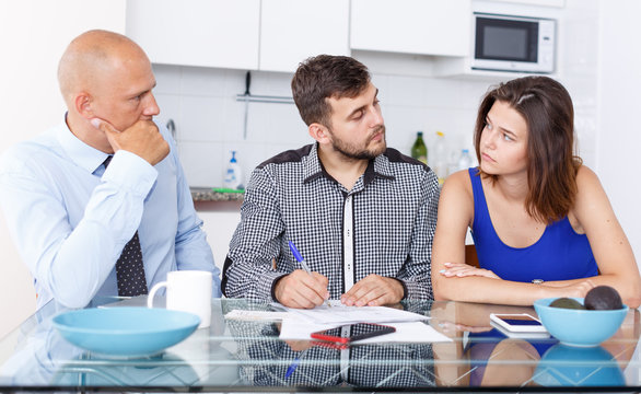 Upset young man and wife signing agreement papers with social worker