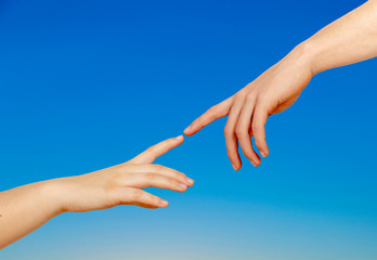 Two hands on a light background, a replica of the plot of Michelangelo's The Creation of Adam
