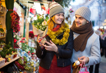Woman and man choosing decorations and Christmas tree