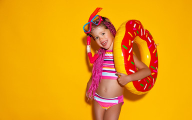 happy child girl in swimsuit with swimming ring donut on colored yellow background