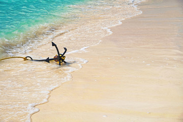 Anchor in waves on white sand beach