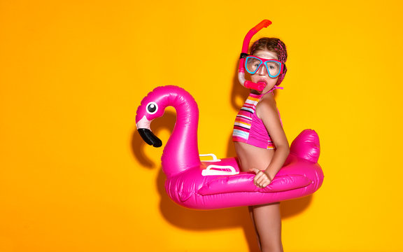 happy child girl in swimsuit with swimming ring flamingo on colored yellow background