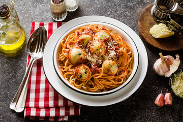 Italian pasta spaghetti with ricotta cheese balls in tomato sauce on the table with parmesan cheese. healthy traditional italian food for the whole family, party or restaurant menu