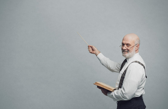 Smiling confident professor teaching and pointing at the blackboard