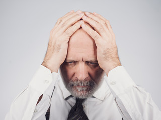 Desperate mature man with head in hands