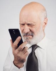 Senior man using a phone and having eyesight problems