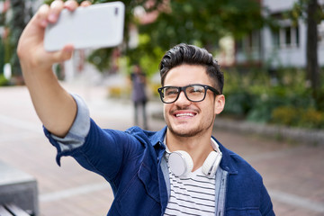 Handsome student taking selfie with smartphone while outdoors on campus