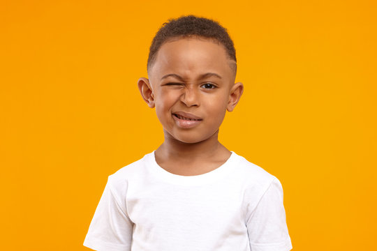 Children, fun and body language concept. Cute African American little boy grimacing against yellow studio wall background, winking at camera, planning joke or trick, wearing casual white t-shirt