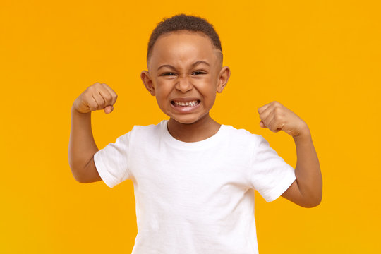 Agression, bullying, negative reaction and emotions. Picture of angry mad little boy of American appearance expressing anger or fury, grimacing and keeping fists clenched, ready to stand for himself