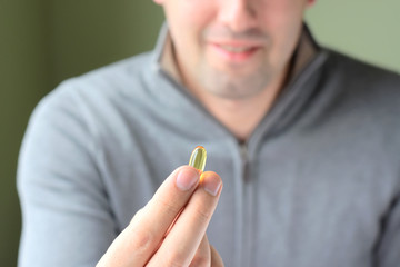 Blurred smiling handsome man in gray sweatshirt on background holding omega 3 soft gel pill in his fingers. Yellow omega 3 vitamin capsules in male hand. Nutritional supplements for people health care