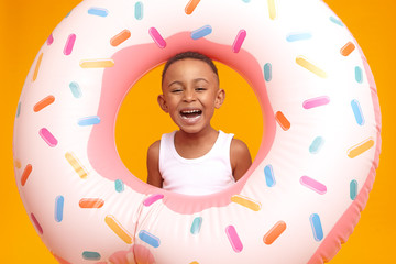 Enjoyment, fun, joy and happiness concept. Cheerful overjoyed dark skinned little boy feeling excited, going to beach with his father, laughing out loud, posing in studio with inflatable circle