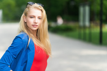 Young blonde woman with colorful dress walking in a park
