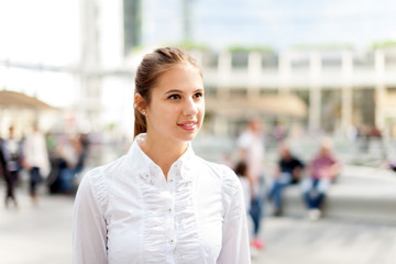 Beautiful young woman walking in a crowded square