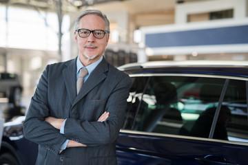 Car dealer salesman in front of a car in his showroom