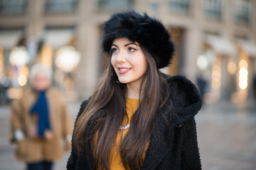 Young woman in winter dress walking in a city