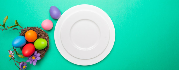 Easter table, place setting. Easter eggs,  empty white plate, green background