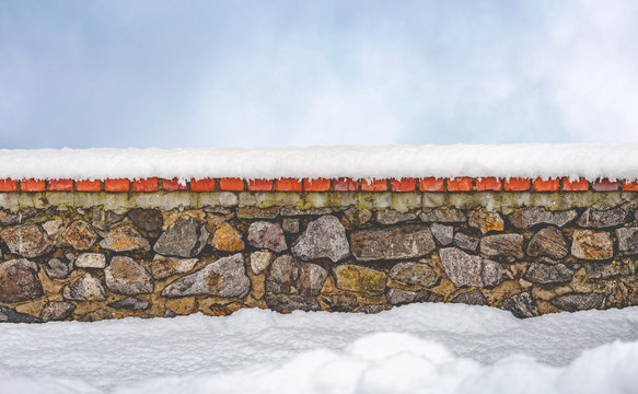 Stone wall covered by fresh snow in winter. A clear sky with soft white clouds appears in the background