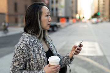 Asian woman in city texting cell phone walking