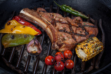 juicy, fried, tender steak with vegetables and sauces on a special stand