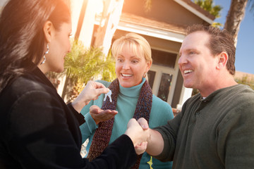 Hispanic Female Real Estate Agent Handing Over New House Keys to Happy Couple In Front of House