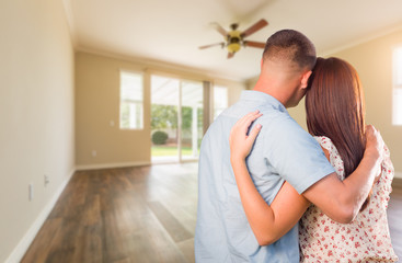 Young Military Couple Looking At Empty Room of New House