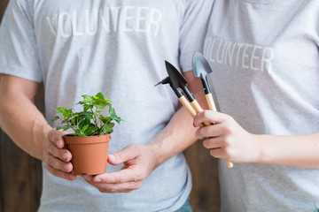 Planting volunteers. Nature care and protection. Couple with houseplant and garden tools.