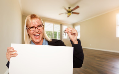 Attractive Young Woman with New Keys and Blank Board In Empty Room of House