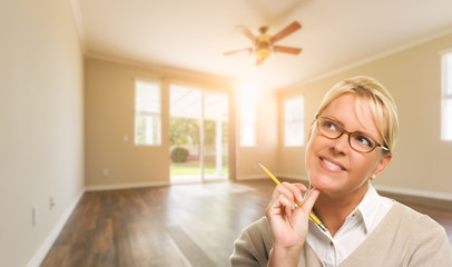 Attractive Woman with Pencil In Empty Room of House