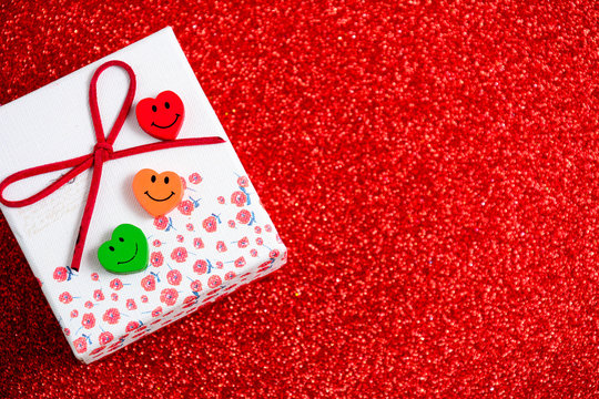Gift box with red ribbon on red background. Close up. Top view. High resolution product. Valentines decorations on red background. Horizontal. Free space for text - Image