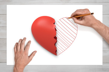 View from above of man's hands on a desk drawing with a pencil the second half of the broken red heart lying on a white sheet of paper.