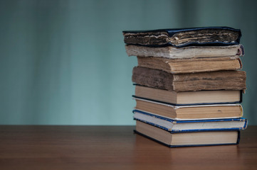 Stack of books on a wooden background. Vintage old books on brown wooden deck tabletop