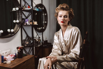 Young attractive actress with wavy hairstyle and red lips in silk robe sitting on chair thoughtfully looking in camera while spending time alone in dressing room