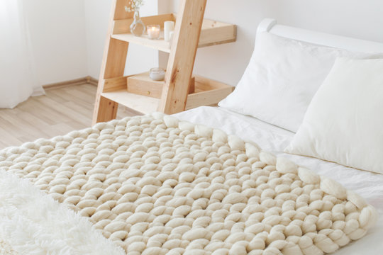 Light beige knitted woolen merino chunky blanket on bed with white linen. Thick yarn. Stylish cozy scandinavian bedroom interior: bed, wooden rack, white wall.
