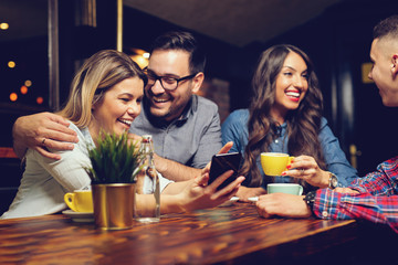 Portrait of cheerful young friends looking at smart phone while sitting in cafe. - Image