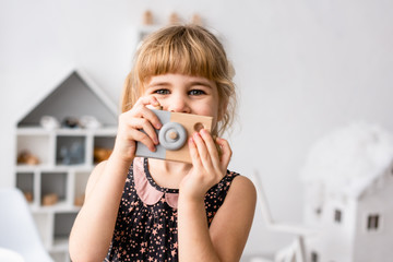 Female toddler looking out of wooden photocamera
