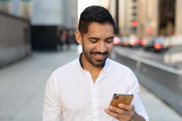 Young Latino Hispanic man in city walking texting cell phone