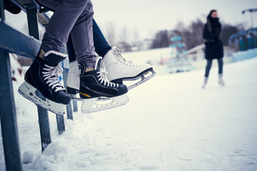 Couple wearing ice skates sitting on a guardrail. Dating in an ice rink.