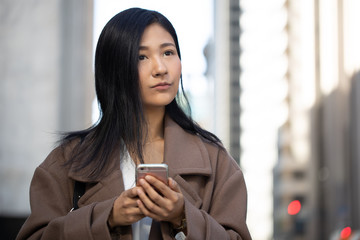 Young Asian woman in city walking texting on cell phone