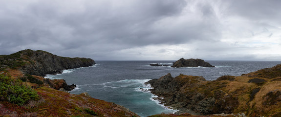 Panoramic landscape view of a Rocky Atlantic Ocean Coast during a cloudy day. Taken in Sleepy Cove, Crow Head, Twillingate, Newfoundland, Canada.