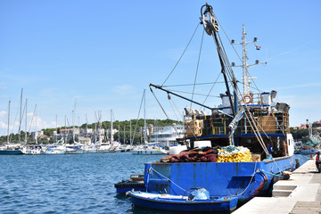 Cargo ship and yachts in a harbor of Pula town, Adriatic sea, Istria region, Croatia