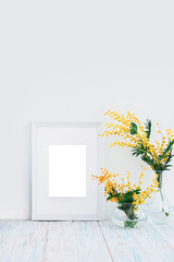Empty white wooden frame and yellow mimosa flowers with copy space. Mockup.