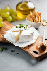 Brie cheese or camembert on cheese platter with crackers, grapes, olive oil. Closeup view, selective focus