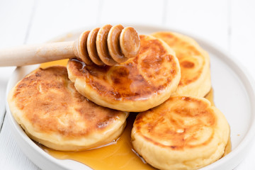 Syrniki, cottage cheese pancakes with honey. Tasty breakfast food. Rich in Calcium cheese pancakes