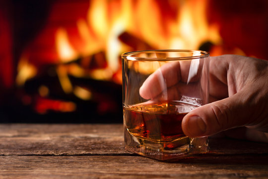 A glass of whiskey in a man hand. Blur burning fireplace background.