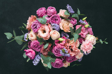 Beautiful bouquet of pink purple peonies, roses and eucalyptus isolated on black background. Top view Fotobehang